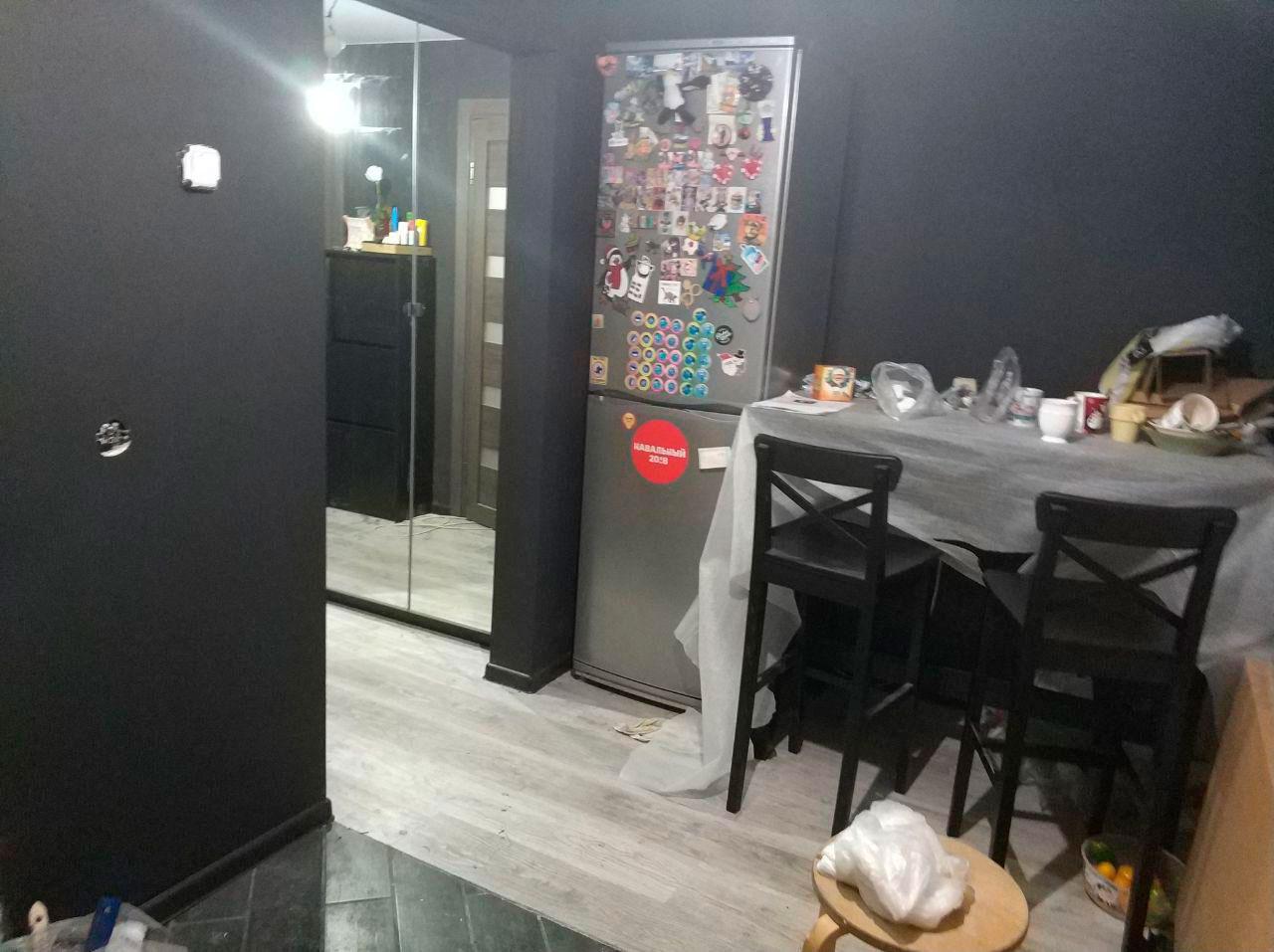 Чёрные стены, холодильник и стол
